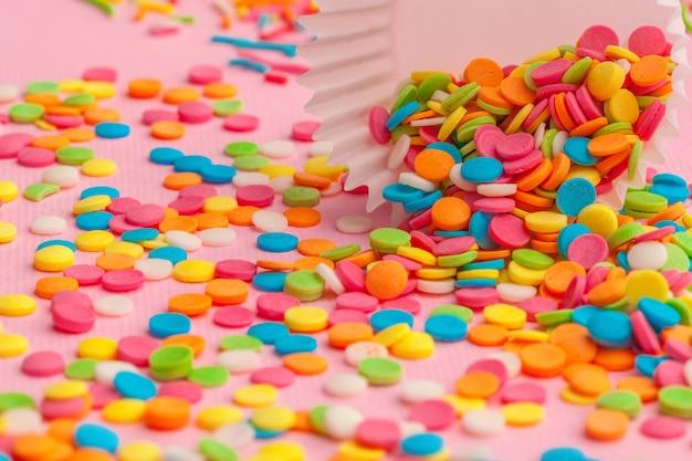 Le sucre saupoudre de la nourriture sur du carton rose
