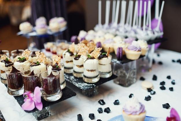 Des sucreries savoureuses recouvertes d'une verrerie violette et blanche servies sur le noir