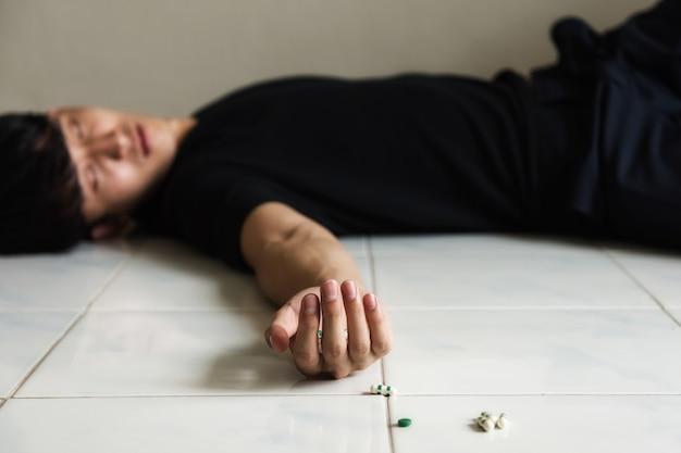 Suicide par overdose pilules sur la main et le plancher