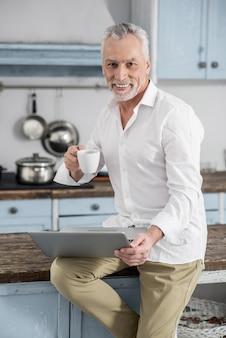 Suis-moi. attractive homme exprimant la positivité tout en buvant du café et en regardant la caméra