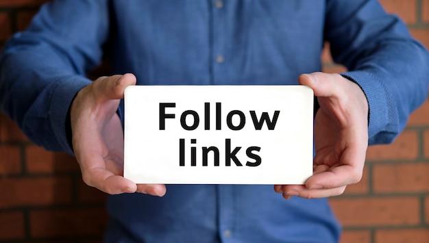 Suivez les liens - concept de référencement entre les mains d'un jeune homme en chemise bleue