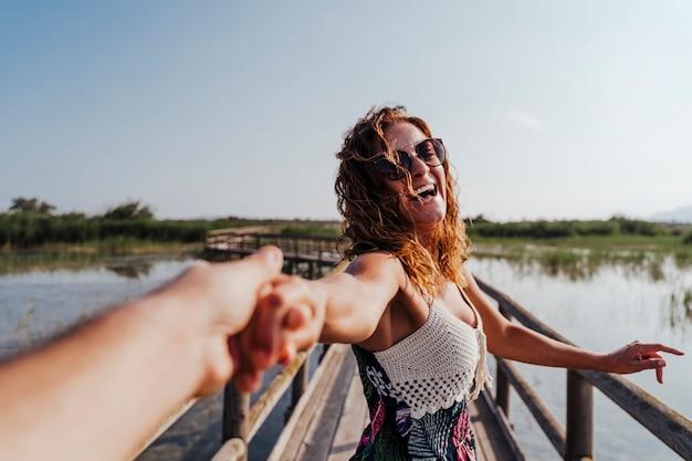 Suivez-moi femme dans un parc naturel tenant la main de son petit ami