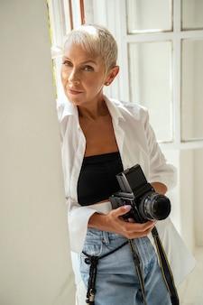 Suivez-moi. heureuse femme tenant une caméra et debout près d'une grande fenêtre
