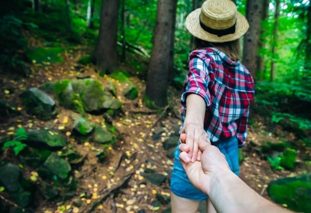 Suivez-moi photo dans les montagnes. femme élégante en chemise à carreaux et chapeau de paille. notion d'envie d'errance. couple randonnée et voyage. tenir la main dans la nature.