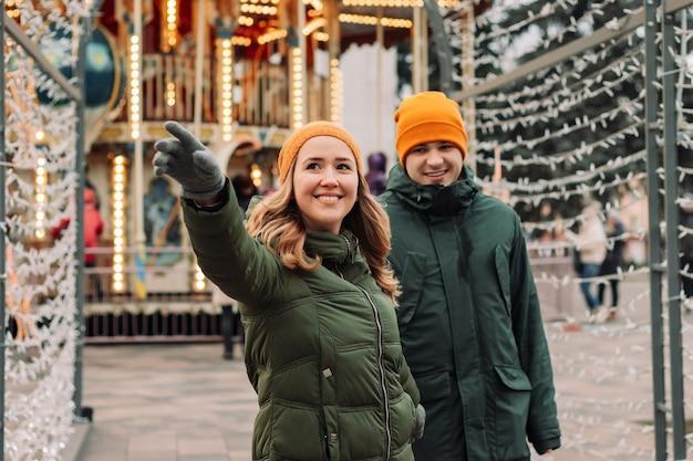 Suivez-moi photo d'un jeune couple d'amoureux attrayant au marché de noël en hiver