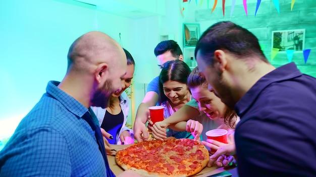 Suivez le plan d'un jeune homme arrivant à une fête universitaire sauvage avec une délicieuse pizza.