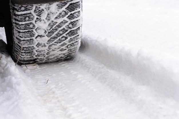 Suivre les roues de voiture sur la neige. pneus de voiture sur route d'hiver. traces des roues de la voiture. pneus sur la neige.