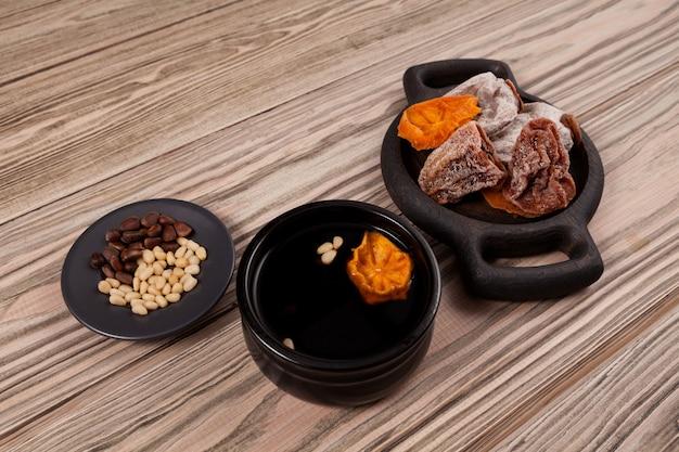 Sujeonggwa- thé aux fruits froid coréen ou punch réfrigéré sur table en bois.