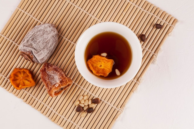 Sujeonggwa - thé glacé coréen. de couleur brun rougeâtre foncé, il est fabriqué à partir de gotgam (kaki séché) et de gingembre et est souvent garni de pignons de pin.