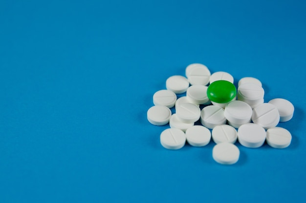 Sujets médicaux faites glisser ou une poignée de pilules se trouvent sur une table bleue. le médicament est pour le virus d'infection de la douleur ou de la maladie