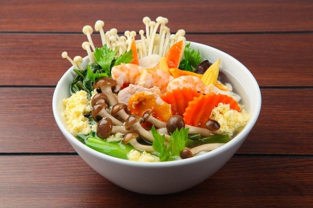 Sukiyaki aux crevettes dans un bol blanc sur fond de bois.