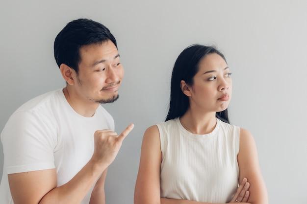Sulk et concilier amant de couple en t-shirt blanc et fond gris.