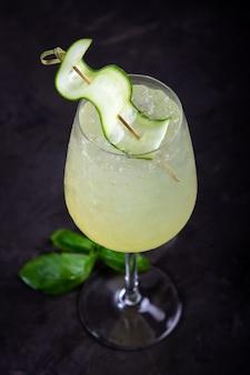 Sumer eau rafraîchissante avec feuilles de concombre et basilic et citron vert dans un verre, cocktail végétarien