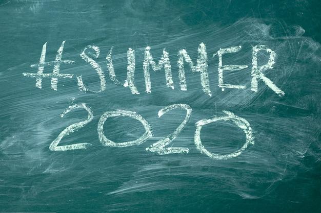 Summer 2020 hashtag écrit à la main à la craie blanche sur un tableau vert.