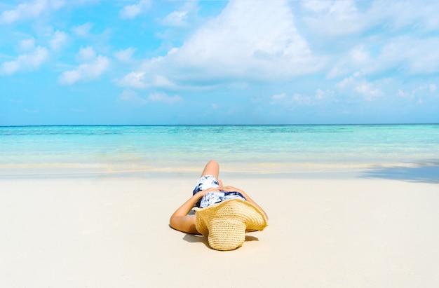 Summer beach holiday woman se détendre sur la plage pendant son temps libre.