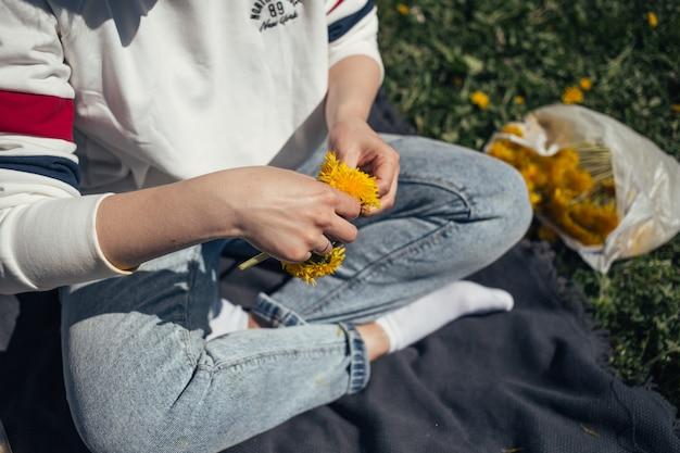 Summer girl tisse une couronne de pissenlits. grand cadre avec pissenlits à la main