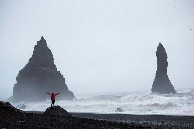 Summertime, femme dans un manteau rose se tenant debout sur une plage de sable noir en islande