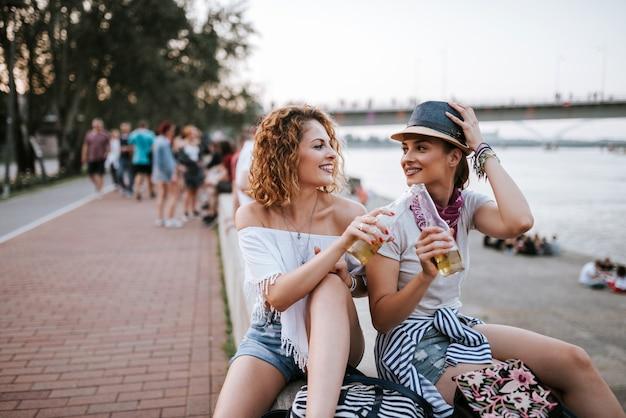Summertime fun. des filles profitant d'un verre près de la rivière dans la ville.
