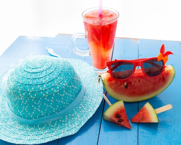 Sunglassed sur pastèque avec chapeau bleu de couleur sur la table,
