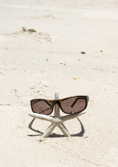 Sunglesses et étoiles de mer sur la plage de sable