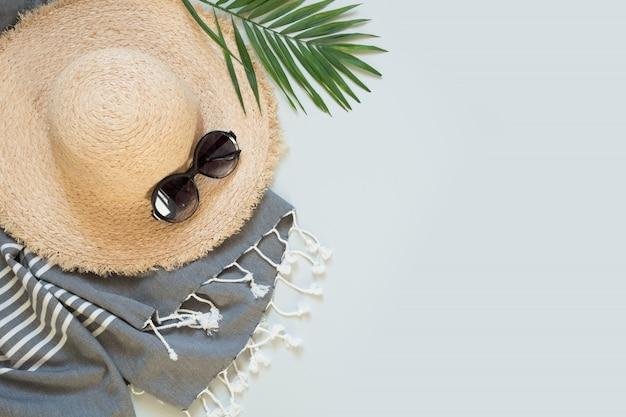 Sunhat de plage de paille et lunettes de soleil sur gris. tenue féminine. vacance d'été.