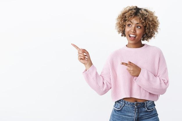 Super concept, c'est intéressant. intriguée et admirative, jolie fille moderne afro-américaine élégante avec perçage et coupe de cheveux afro juste bouche ouverte curieuse, pointant et regardant le coin supérieur gauche