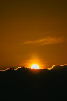 Super coucher de soleil sur le fond d'écran des nuages noirs sur des tons maussades et des tons orange