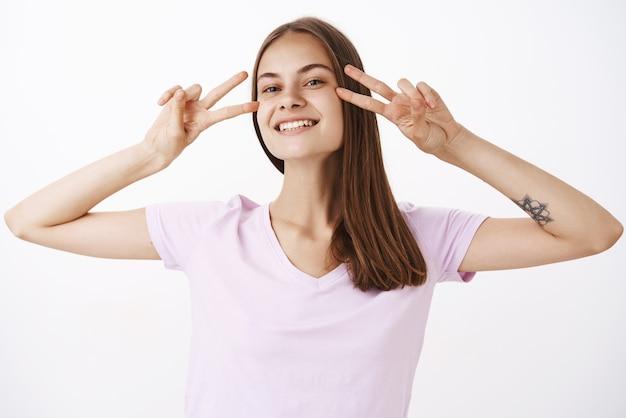 Super femme caucasienne heureuse et insouciante avec tatouage sur le bras montrant des signes de disco ou de paix près des yeux et souriant avec un regard joyeux dansant passer des week-ends amusés et divertis