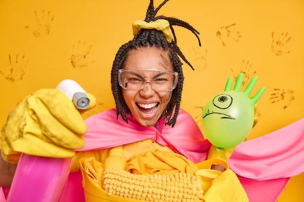 Une super-femme joyeuse dans des gants en caoutchouc de manteau rose, des lunettes de protection, tient une bouteille de distribution et un ballon gonflé nettoie toutes les pièces de la maison isolées sur un mur jaune