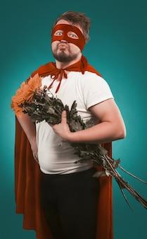 Super héros amoureux d'un bouquet de fleurs pour son amoureux. homme en costume de super-héros tenant un bouquet de chrysanthèmes croisa les lèvres pour un baiser