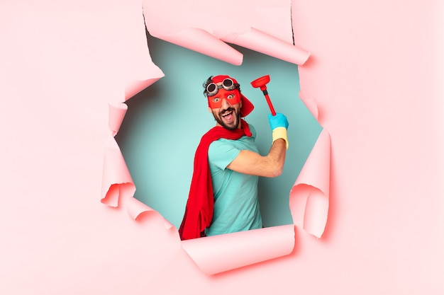 Super-héros avec des articles de salle de bain derrière un mur de papier cassé