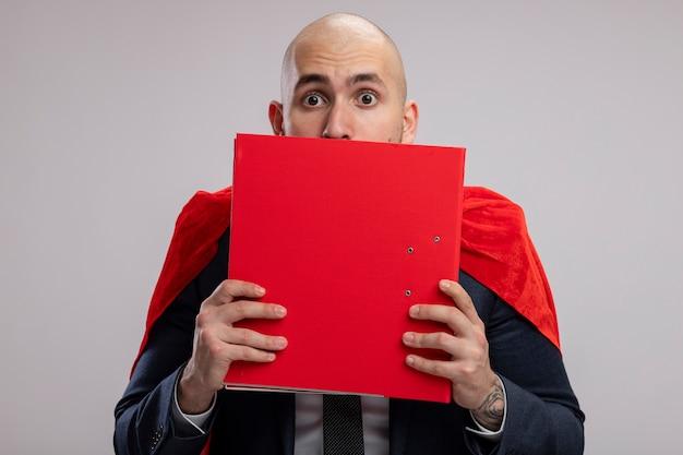 Super héros barbu homme d'affaires en cape rouge tenant un dossier couvrant son visage derrière elle furtivement plus de peur debout sur un mur blanc
