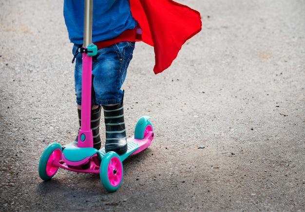 Super-héros bébé garçon utilisant un adorable concept de scooter