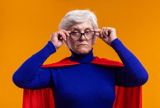 Super-héros femme senior avec des lunettes portant une cape rouge regardant la caméra avec un visage sérieux debout sur fond orange