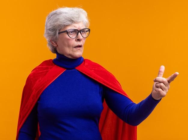 Super-héros femme senior avec des lunettes portant une cape rouge regardant de côté avec une expression confuse pointant