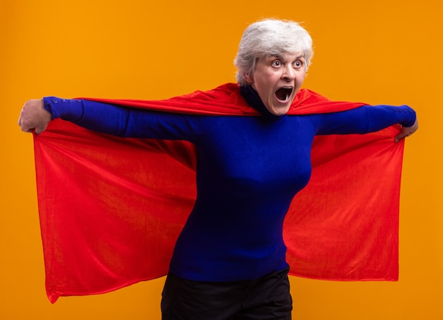 Super-héros femme senior portant une cape rouge à côté surpris en criant tenant sa cape va voler debout sur orange