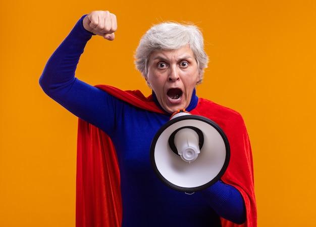 Super-héros femme senior portant une cape rouge criant au mégaphone avec le poing fermé debout sur fond orange