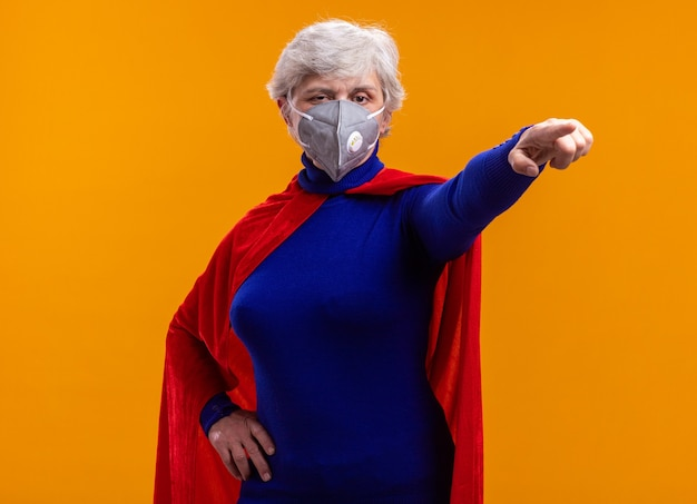 Super-héros femme senior portant une cape rouge et un masque de protection faciale pointant vers quelque chose avec un visage sérieux debout sur fond orange
