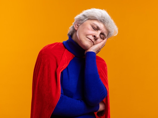 Super-héros de femme senior portant une cape rouge penchée sur la paume, geste de sommeil avec les yeux fermés