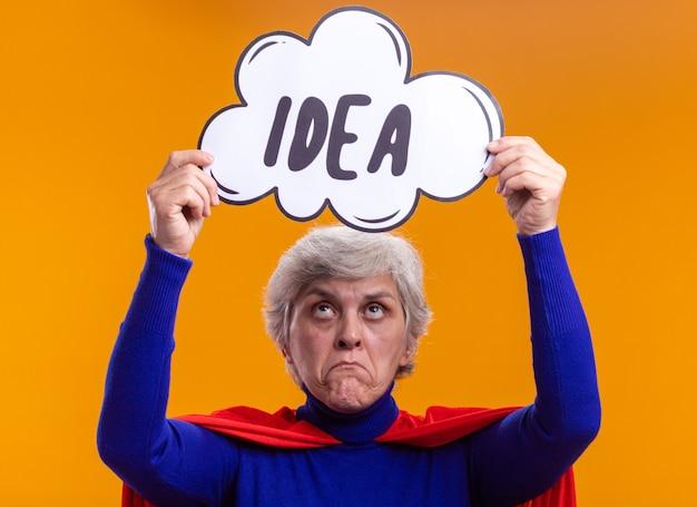 Super-héros femme senior portant une cape rouge tenant un panneau de bulle de dialogue avec une idée de mot au-dessus de sa tête faisant la bouche tordue avec une expression déçue