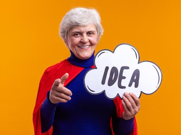 Super-héros femme senior portant une cape rouge tenant un panneau de bulle de dialogue avec une idée de mot pointant avec l'index à la caméra, heureux et positif, debout sur fond orange
