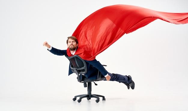 Super-héros d'homme avec le professionnel de directeur de chaise de bureau de manteau rouge