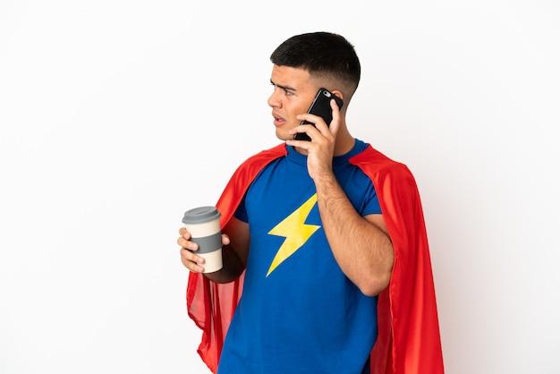 Super héros sur un mur blanc isolé tenant du café à emporter et un mobile
