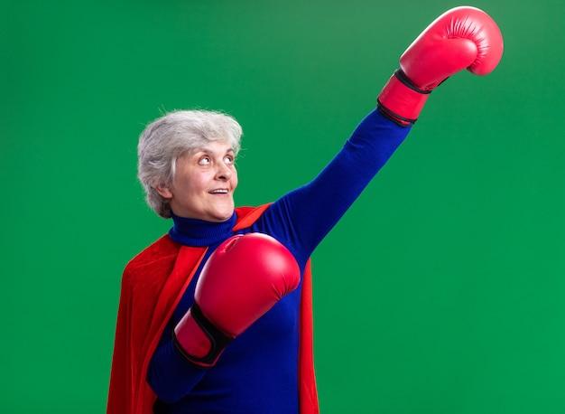 Super-héros senior femme portant une cape rouge avec des gants de boxe dans la victoire pose heureux et confiant debout sur vert