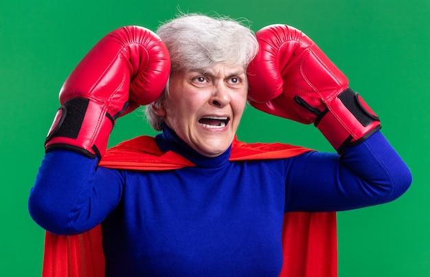 Super-héros senior femme portant une cape rouge avec des gants de boxe frustré et fou fou touchant sa tête debout sur fond vert