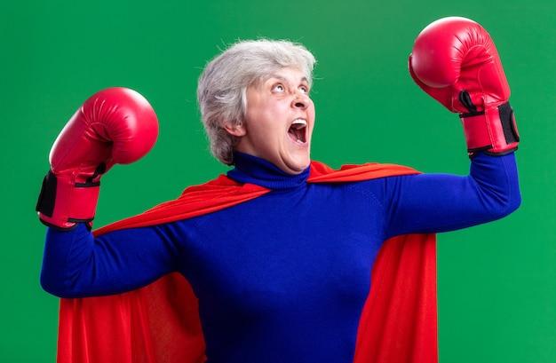 Super-héros senior femme portant une cape rouge avec des gants de boxe posant comme un gagnant excité