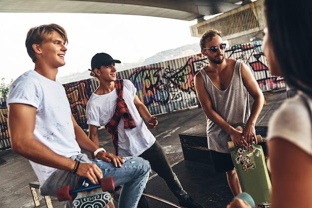 Super journée entre amis. groupe d'amis patineurs discutant en se tenant sous le pont à l'extérieur