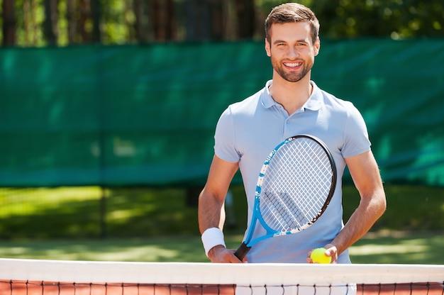 Super journée pour jouer ! joyeux jeune homme en polo tenant une raquette de tennis et une balle en se tenant debout sur un court de tennis