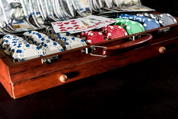 Un super prix de grand casino - une caisse pleine de jetons, de dollars et de cartes à jouer sur fond noir