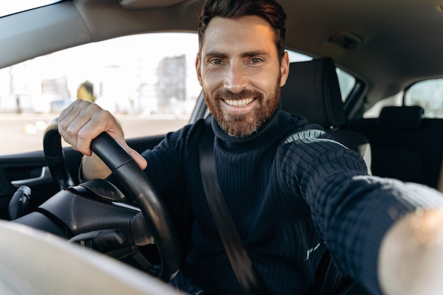 Super selfie. bel homme barbu tenant une caméra et faisant un selfie assis dans la voiture au siège du conducteur et regardant la caméra avec plaisir sourire